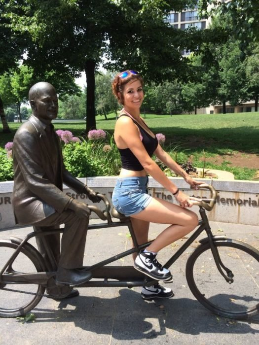 Chica en bici con estatua