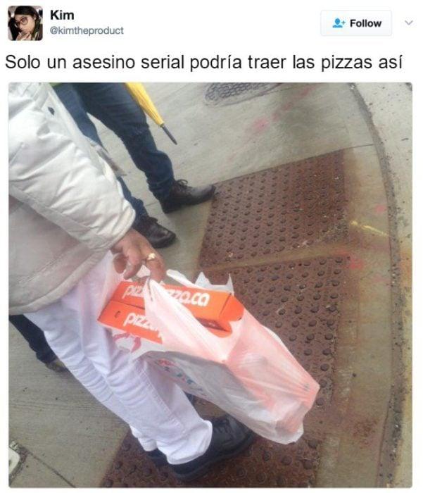 hombre lleva la pizza verticalmente
