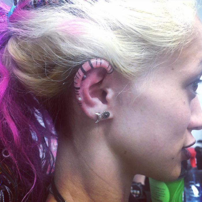 Tatuaje de muchas lineas en el cartilago de mujer