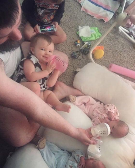 papá dando biberón a tres bebés