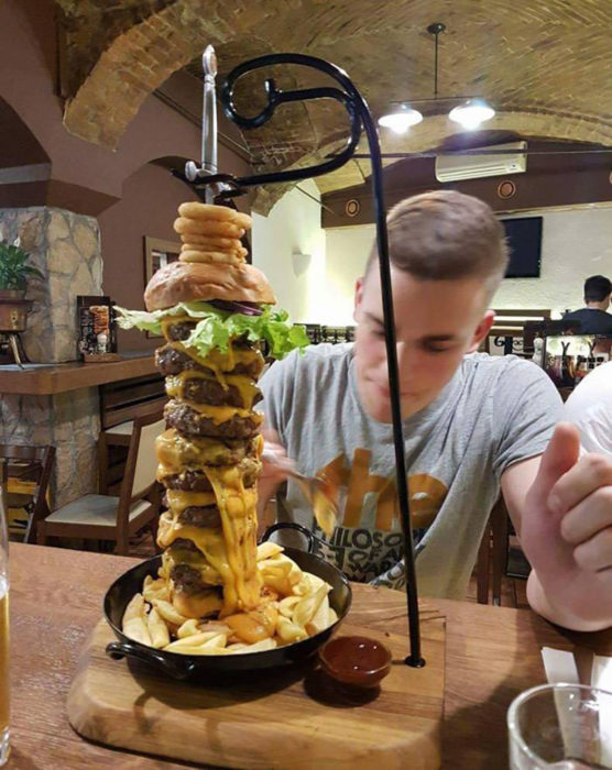 hombre comiendo una hamburguesa de varios pisos