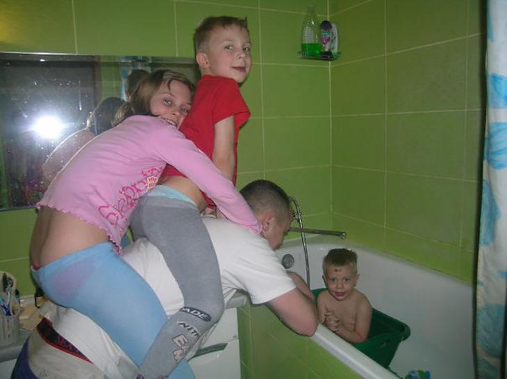 papá bañando a un niño mientras carga otros dos