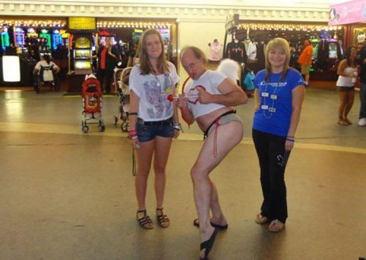 hombre vestido de cupido con dos mujeres al lado
