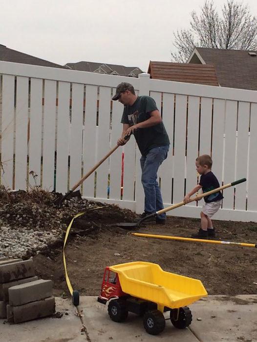 padre e hijo recogiendo hojas en el patio