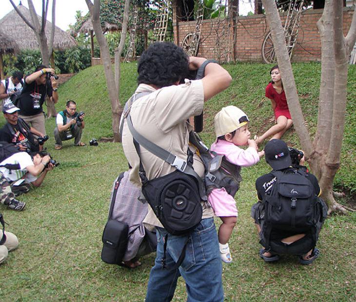 papá fotógrafo cargando a su bebé
