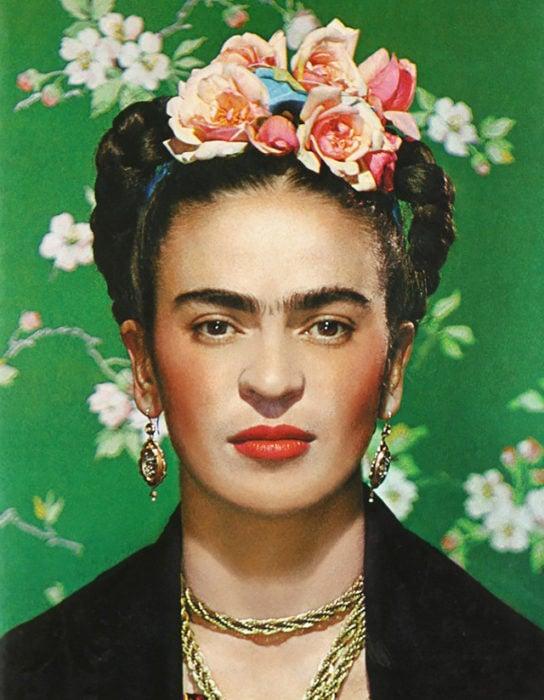Frida fondo verde flores en la cabeza artista pintora mexicana