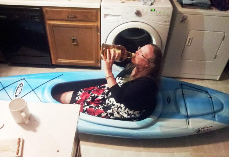 mujer en kayak tomando de una botella