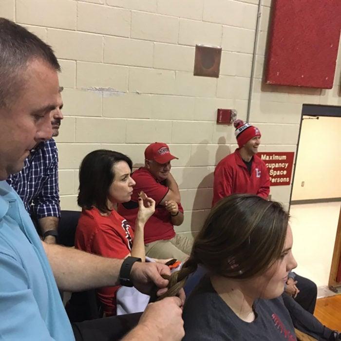 papá trenza el cabello de su hija adolescente