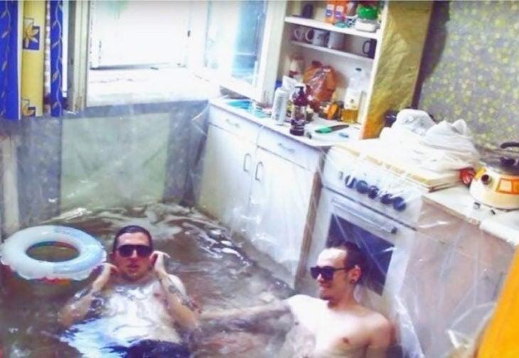 hombres improvisan una piscina con hule en la cocina