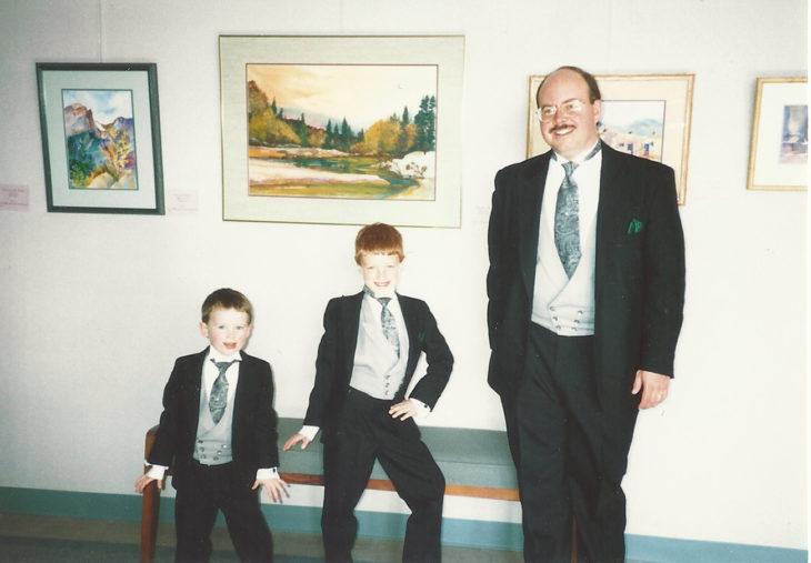 papá y dos hijos con traje, uno posa afeminado