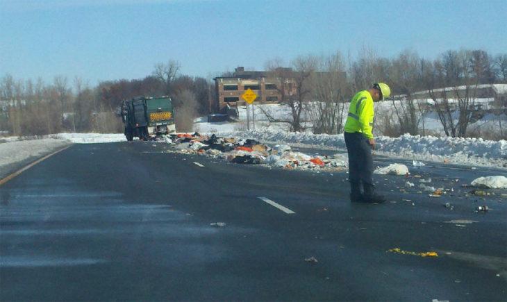 camión de basura tirando su contenido a lo largo del camino