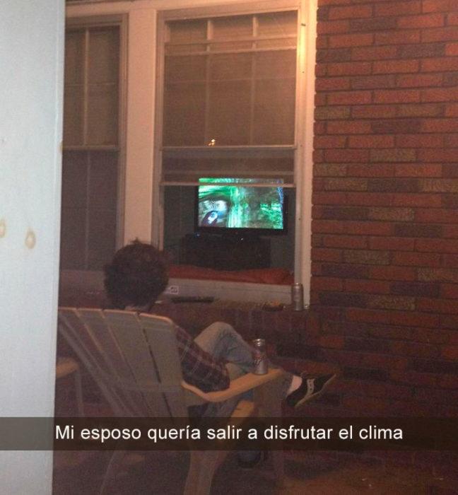hombre viendo la tele desde afuera