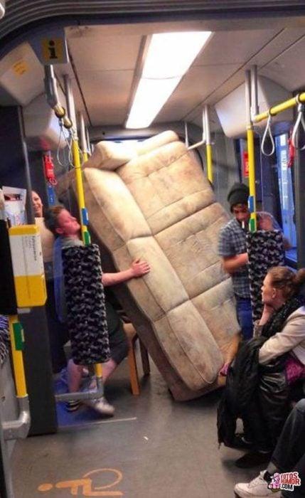 chico llevando sillón en el transporte público