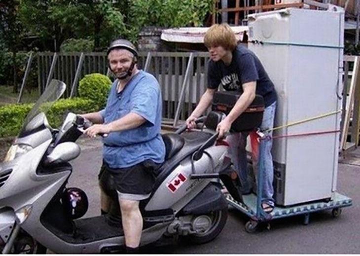 joven sosteniéndose de motocicleta para llevar un refrigerador