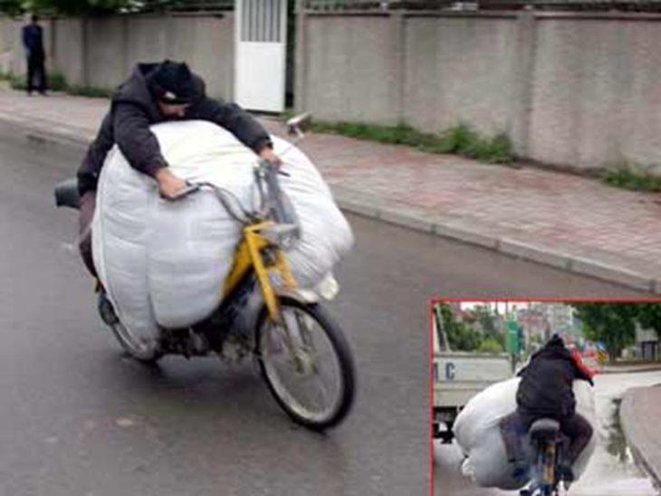 hombre lleva un gran paquete mientras va en su bicicleta