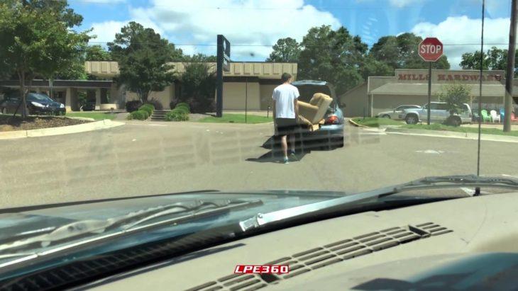 joven intentando meter sillón en la caja de su vehículo