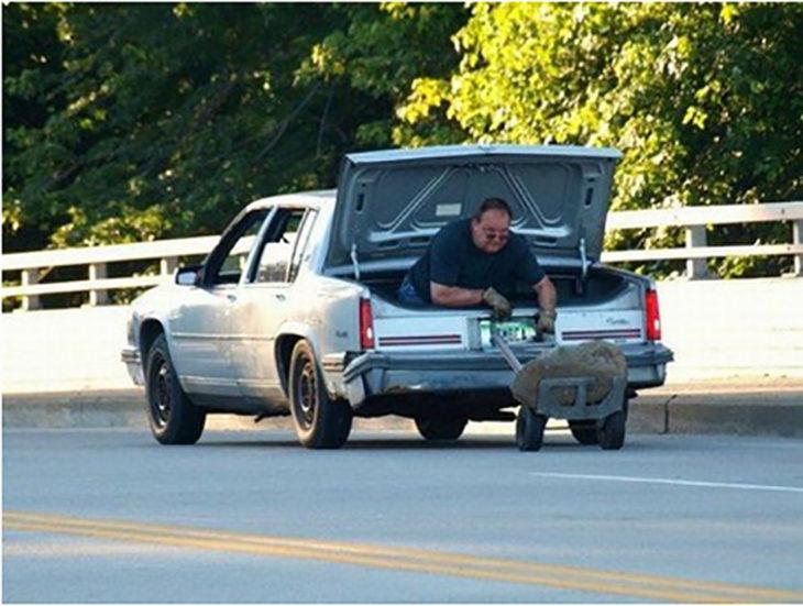 Hombre sujetando diablito desde la cajuela de un coche