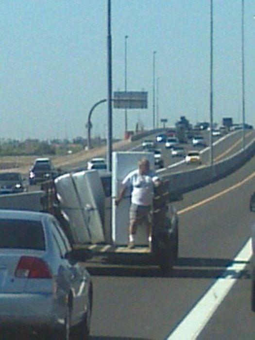 Hombre deteniendo electrodomésticos desde vehículo en movimiento