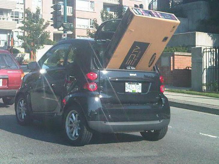 Pequeño vehículo llevando un gran televisor