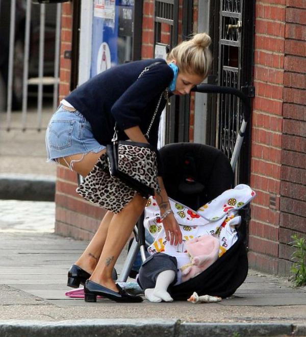 Mujer intenta recoger a su bebé del piso con el celular en el oído