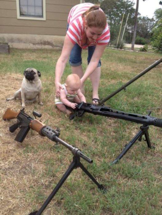 Mujer deja a su bebé jugar con rifles
