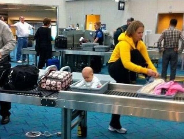 Mamá atándose las cintas de los zapatos mientras su bebé pasa por inspección en aeropuerto