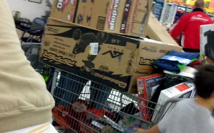 Niño dormido en carrito de compras y arriba va lleno de cajas