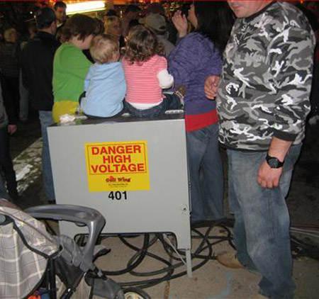 Niños sentados en caja que dice: peligro alto voltaje