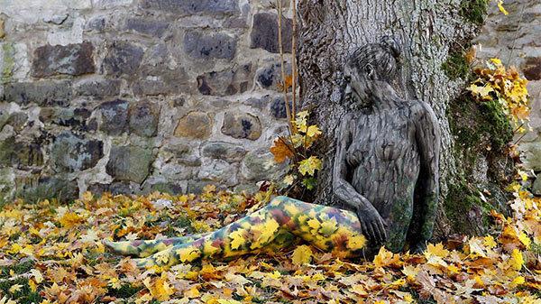 mujer pintada como arbol y hojas