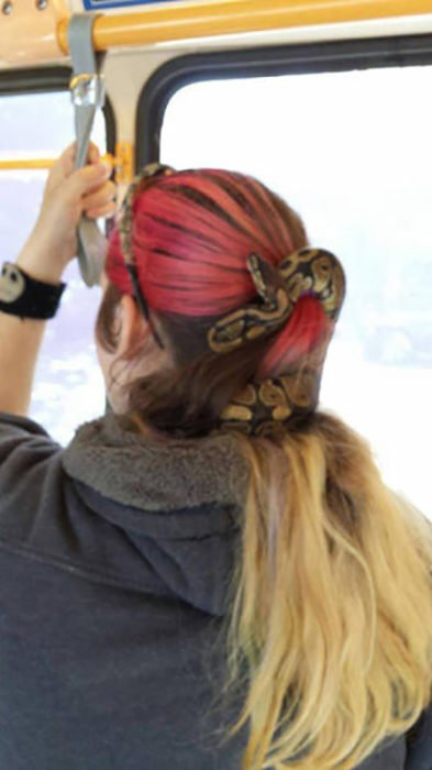 chica con una serpiente en el cabello en lugar de liga