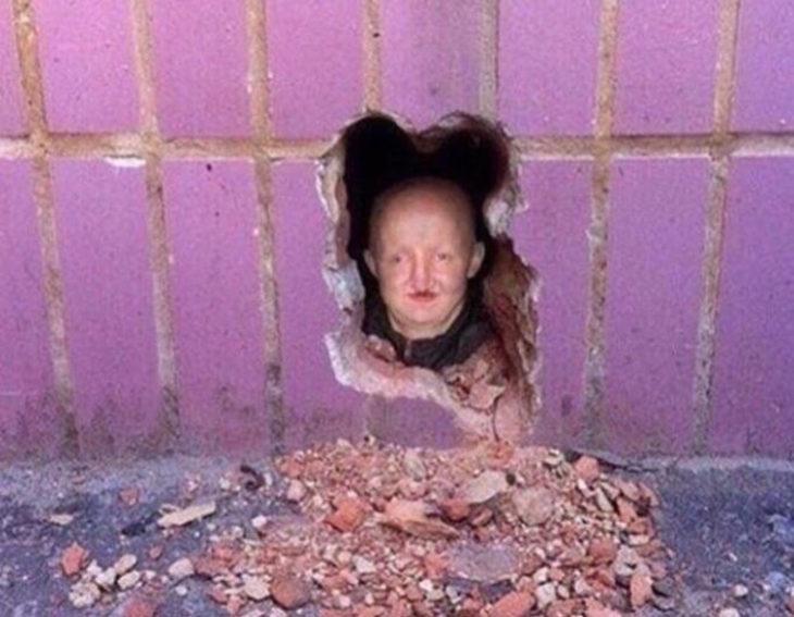 cabeza de maniquí dentro de hoyo en el muro