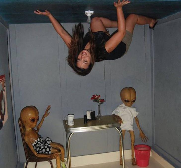 Chica en un cuarto extraño con marcianos