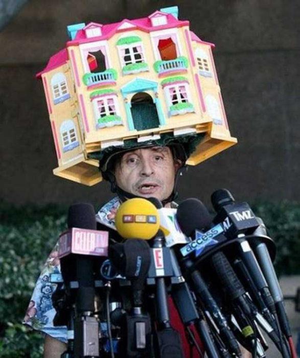 hombre con casa de muñecas en la cabeza