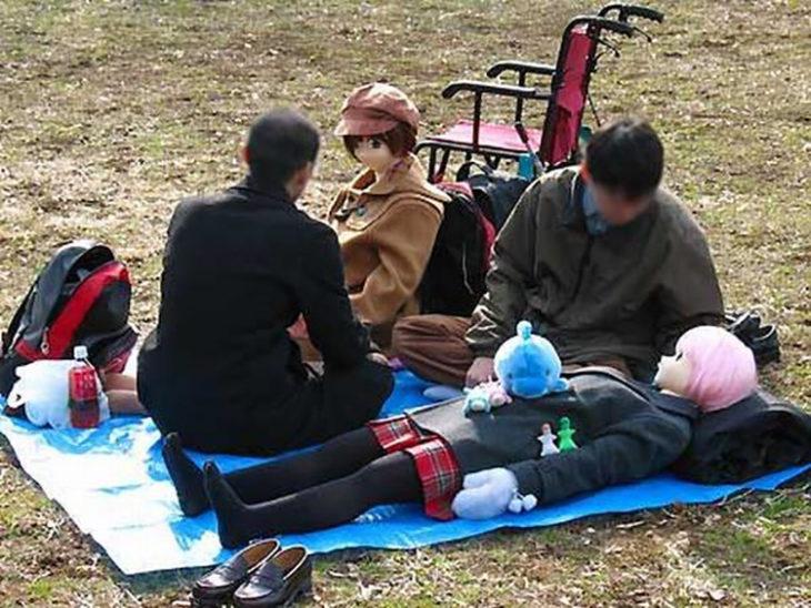 jóvenes en un parque con unas muñecas