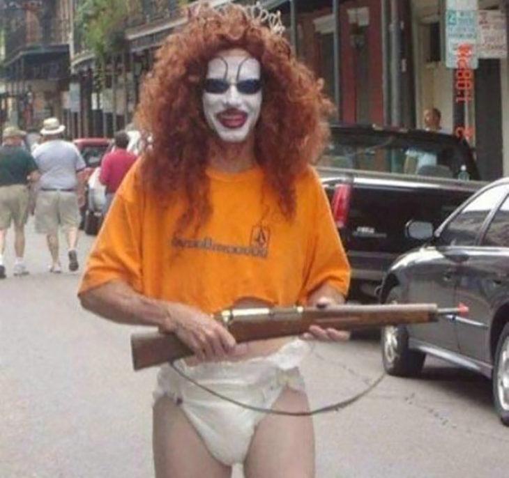 hombre con maquillaje usando pañal y un arma