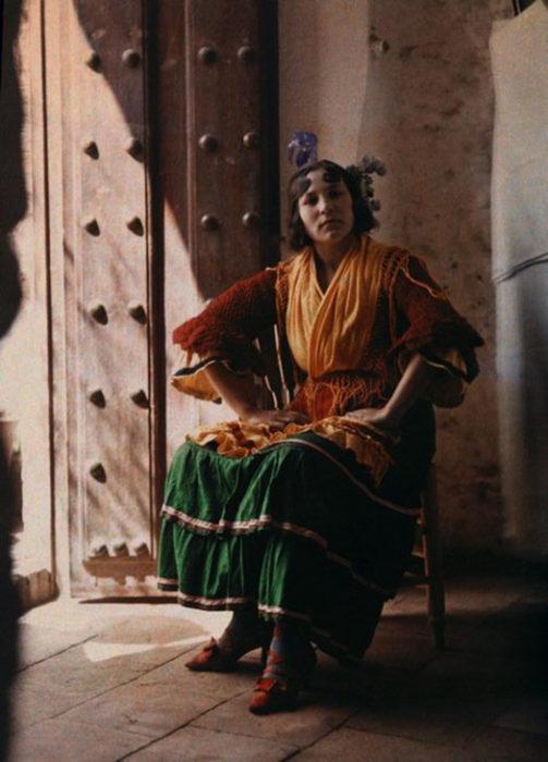 gitana posando en una silla usando su vestido tipico