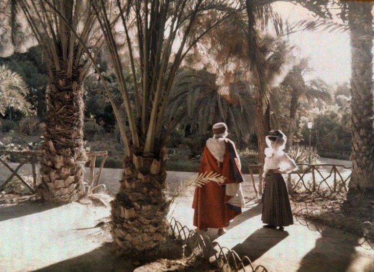 Fotografía antigua de dos visitantes en un jardín de Argelia