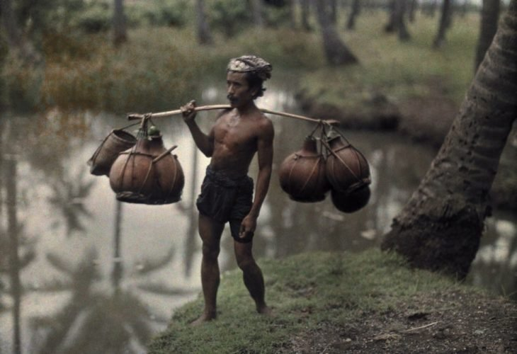 fotografía antigua de mozo cargando agua en calabazas