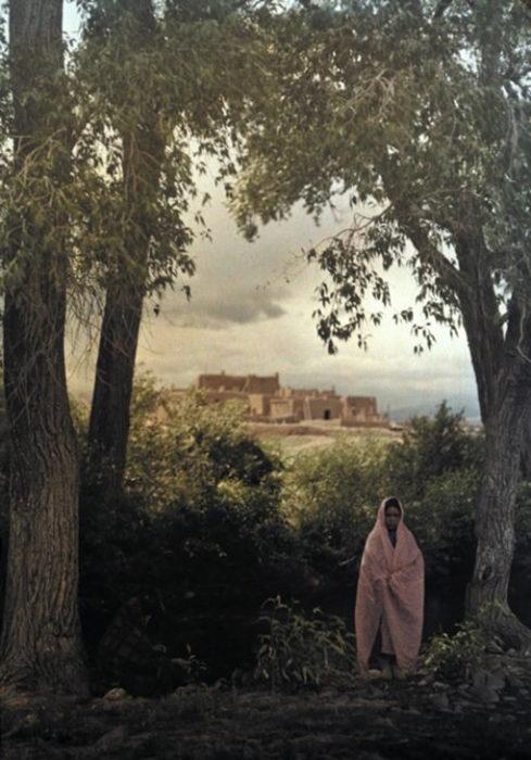 fotografía antigua de mujer posando a las afueras de su pueblo