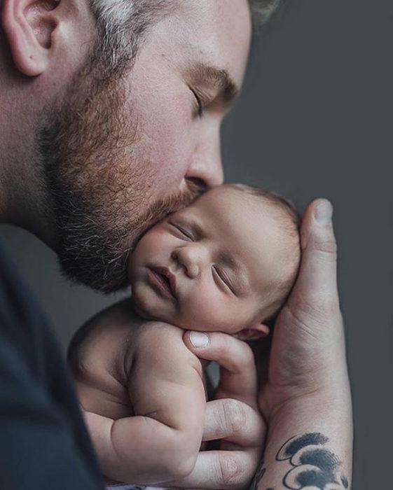 papá besando a su bebé