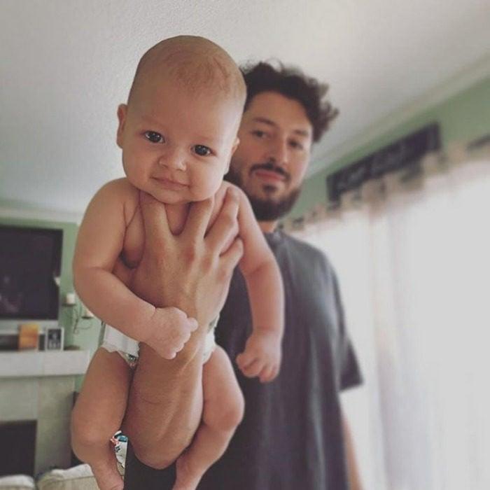 padre cargando a su bebé una mano