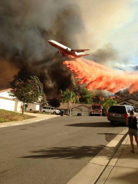 Avión pasando por bosque en fuego para apagarlo