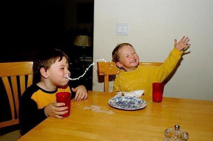 niño escupiendo leche mientras se ríe