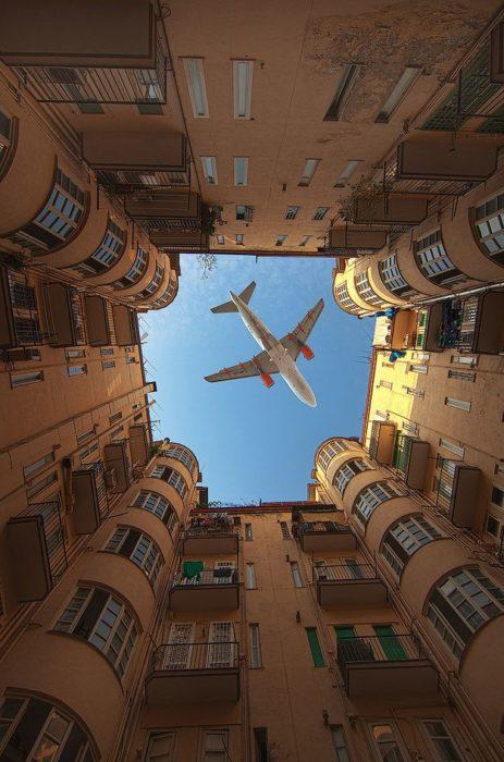 momento justo que avión pasa ente edificio