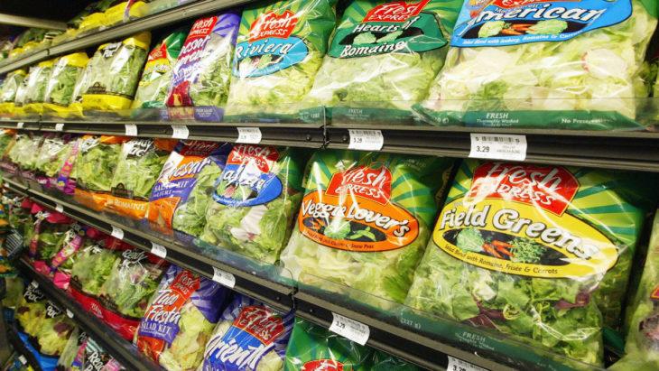 refrigerador de supermercado lleno de bolsas de ensalada preparada