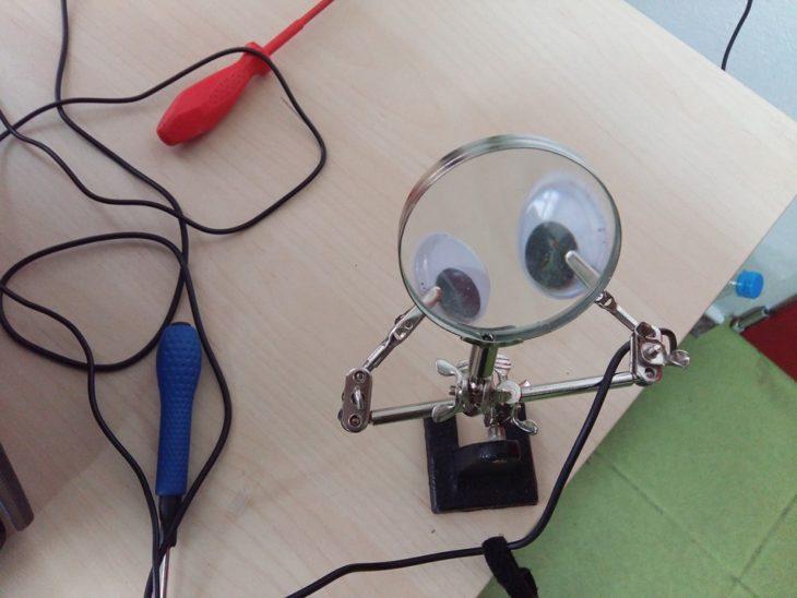 lupa para circuitos usando pinzas para sostener ojos locos