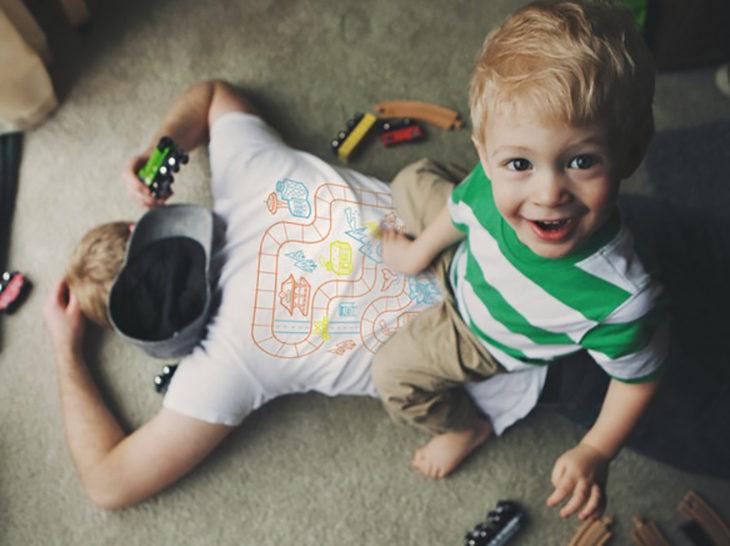 niño jugando en espalda del padre que esta cansando