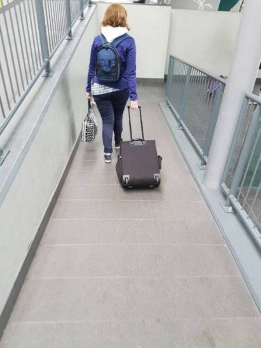 mujer transportando maleta de manera incorrecta