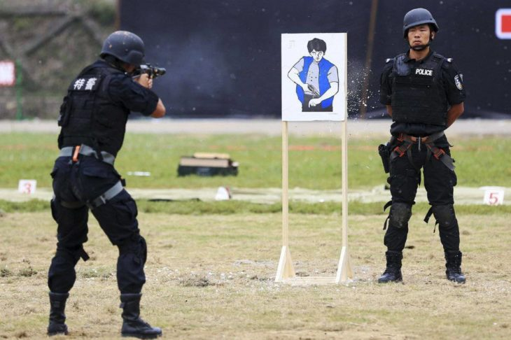 policías en campo de tiro uno de ellos distraído