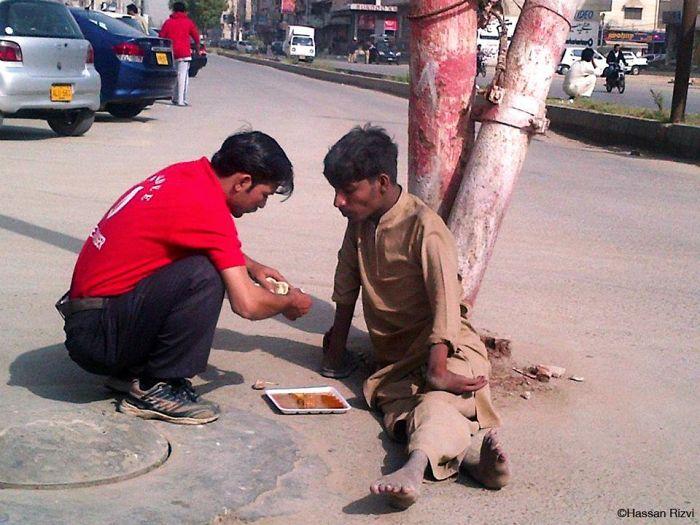 Persona dándole de comer a un hombre